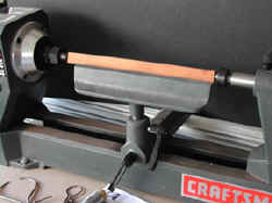 Wood lathe demonstrates the turning of a  wire tool handle.